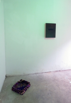 Muslim rug for praying, folded in-situ as an origami box, in the background a painting by Ion Macareno