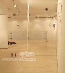 Frontal view of 'Ariadne', white cotton sheet torn by the artist and two red clay figures, dimensions variable